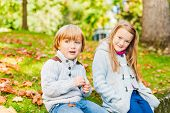 Two adorable kids having fun outdoors on a nice sunny autumn day
