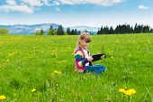 Cute little girl playing with tablet pc outdoors