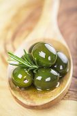 picture of kalamata olives  - wooden spoon with green olives olive oil and some fresh rosemary on a cutting board - JPG
