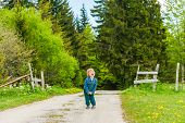Cute toddler boy standing in the middle of the forest road and screaming