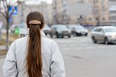 pic of ponytail  - A woman with a ponytail stands waiting or watching close to the street with cars in the city - JPG