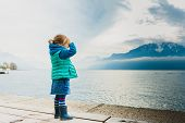 Adorable toddler girl playing by the lake, looking at the mountains, wearing, rain boots, jeans skir