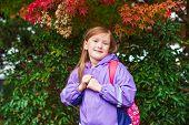 Little schoolgirl with backpack, wearing purple rain coat