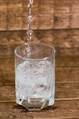 splash in water from a glass with ice, is isolated on a brown background