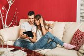 Young Couple Sharing Music On Digital Tablet In Sofa At Home