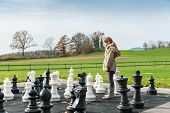 Adorable little girl playing with huge chess in a park on a cold day