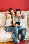 Young Couple Listening To Music Via Tablet And Holding Thumbs Up