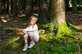 Adorable little girl hiking in the forest on a nice day