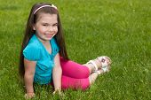 Happy Little Girl On The Grass