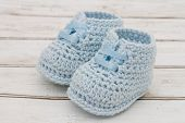 stock photo of booty  - Retro Baby Booties Pale Blue Baby Booties on a grunge wood background - JPG