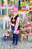 Outdoor portrait of a cute little girl in a city on a nice sunny day, standing next to flower shop,