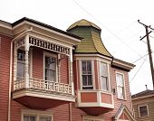 picture of shingles  - Detail of pink Victorian house featuring a small balcony porch carved spindles and a turret with green fish scale shingles - JPG