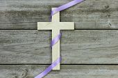 Wooden cross with purple ribbon hanging on rugged wood background