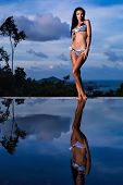 pic of swimsuit model  - Pretty brunette model in blue striped bikini posing at the pool with reflection of the evening sky - JPG