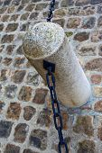 foto of stud  - Stone stud and chain on a cobbled square - JPG