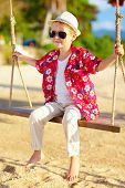 Cute Stylish Boy On Swings At The Beach