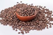 isolated ceramic bowl with pile of coffee beans are scattered