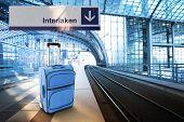 Departure For Interlaken, Switzerland. Blue Suitcase At The Railway Station