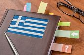 Notebook on a desk with the flag of Greece