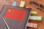 Notebook on a desk with the flag of China