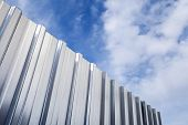 Shining Corrugated Metal Fence And Blue Cloudy Sky