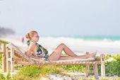 Woman sunbathing on tropical beach.