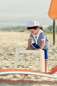 Playful Toddler Dressed As A Sailor Standing On A Beach And Climbing On A Plastic Table. Photo With