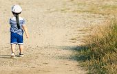 Sweet Toddler Dressed As A Sailor Walking With Determination On A Gravel Road. Photo With Untraditio