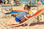 Toddler Dressed As A Sailor Climbing On A Tilted Sunbed On A Beach. Photo With Untraditional Color R