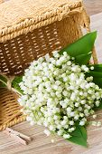 stock photo of lillies  - lilly of the valley flowers posy in basket  on wooden background - JPG