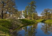 stock photo of cupola  - Church with golden cupola next to water in spring - JPG