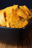 picture of doritos  - Nacho cheese flavored tortilla chips in a dark bowl on a wooden table - JPG