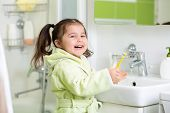Smiling little girl brushing teeth in bath