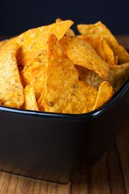foto of doritos  - Nacho cheese flavored tortilla chips in a dark bowl on a wooden table - JPG