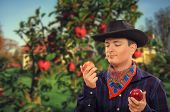 stock photo of cowboys  - Cute young cowboy holding red apple in each hand - JPG