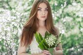 stock photo of lily  - Portrait of beautiful young woman with lily of the valley - JPG