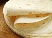 image of whole-wheat  - stack of homemade whole wheat flour tortillas on a wooden table - JPG