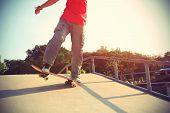 picture of skateboard  - skateboarder legs riding skateboard at skatepark ramp - JPG