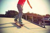 stock photo of skateboard  - skateboarder legs riding skateboard at skatepark ramp - JPG