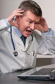 Doctor Gestures In Despair At Information On Laptop
