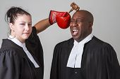 pic of toga  - woman hammering a man on the head with a gavel both wearing canadian lawyers toga - JPG