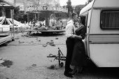 picture of trailer park  - man and woman is hidden from view behind a trailer in the park with attractions - JPG