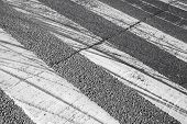 picture of pedestrian crossing  - Tire tracks over pedestrian crossing road marking on dark asphalt - JPG