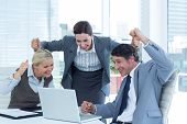 stock photo of cheers  - Cheerful business people cheering in front of laptop at office desk - JPG
