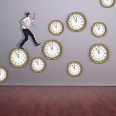 stock photo of running-late  - Geeky businessman running late against room with wooden floor - JPG