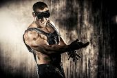 stock photo of mines  - Brutal muscular dirty man expressing aggression over dark grunge background - JPG