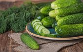 stock photo of cucumber slice  - Fresh cucumbers and slices on a wooden table - JPG