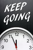foto of midnight  - The phrase Keep Going in white text on a blackboard above a modern wall clock with the hands pointing at midnight - JPG
