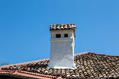 image of chimney  - Front view of a white chimney on a house roof on blue sky background - JPG