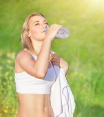 picture of sportive  - Happy tired woman drink water after workout in the park - JPG